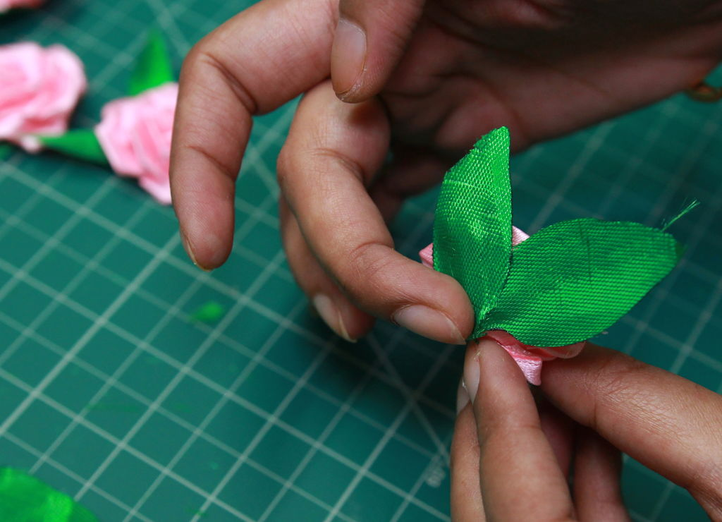 gluing two or three leaves to each rose