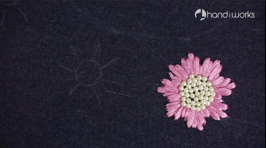 stitching white pearls at the center of flower